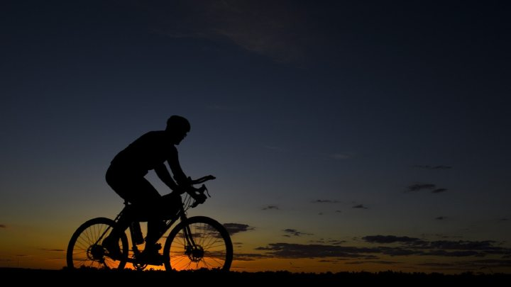 Man on electric bike at sunset