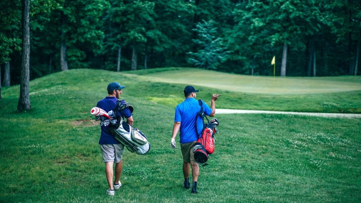 Golfers carrying their bags without their golf trolleys