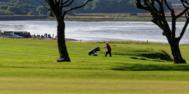 Man with electric golf trolley on golf course