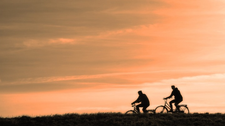 Silhouette of two cyclists against sunset sky