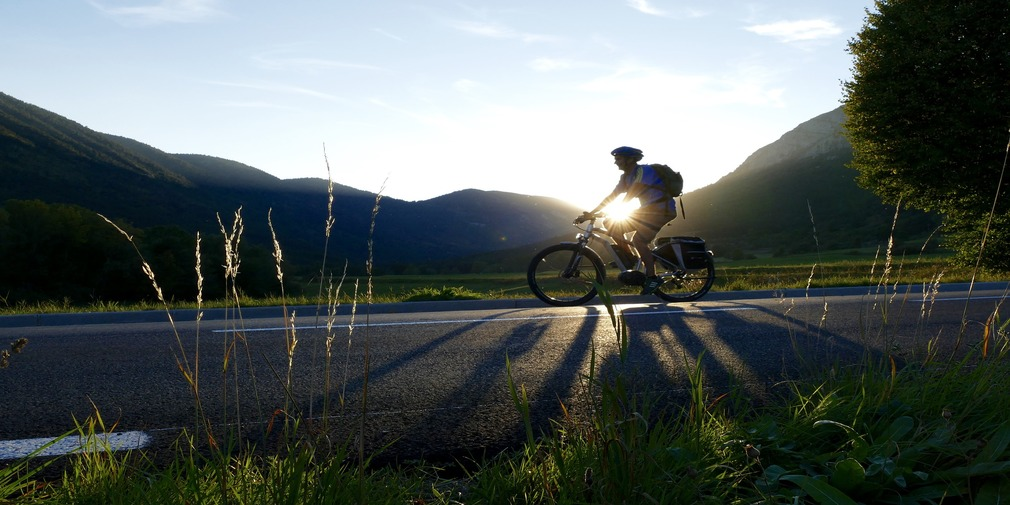 Man on bicycle with sunset and hills in the background