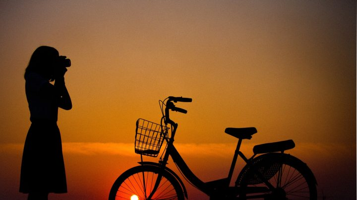 Silhouette of girl taking photo and bike