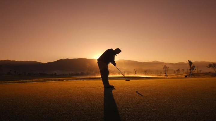 Silhouette of man playing golf against the sunset