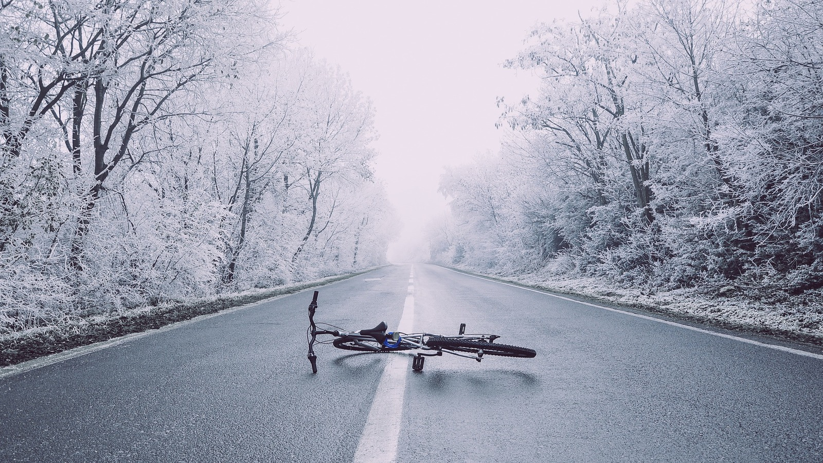 Bike laying in middle of road in frosty weather